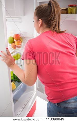Young gourmand woman think what to take to eat from fridge