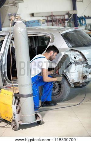 mechanic welding damage on car
