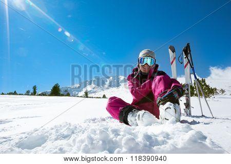 Female skier resting on the ski slope