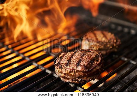 steaks on the grill with hot flames shot with selective focus
