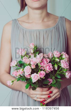 Wedding bouquet of flowers, young bridesmaid holding a bouquet of pink roses.