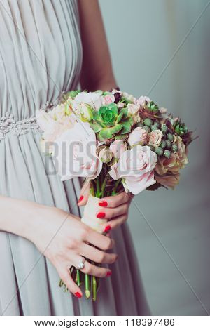 Wedding bouquet of flowers, young bride holding a bouquet of flowers. Image of wedding dress and floral bouquet.