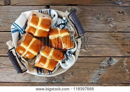 Hot Cross Buns in a basket, over rustic wood