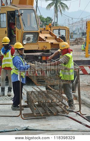 Group of construction workers fabricating column reinforcement bar