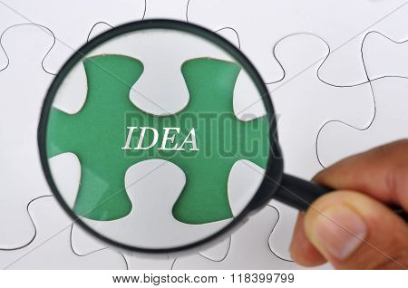 Hand Holding Magnifying Glass Seaching Missing Puzzle Pieces