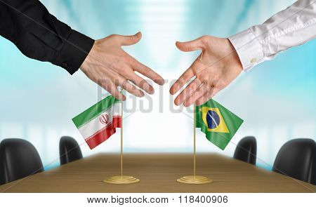 Iran and Brazil diplomats shaking hands to agree deal