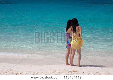 Duo Tourists On The White Sand Beach