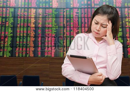 Business woman see tablet screen for loss value and feel pain strain with stock board background