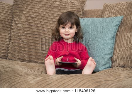 Young girl looks up from tablet with a smile