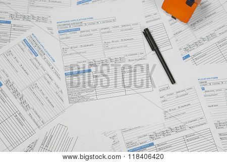 Mortgage application forms with foam house and black pen sitting on top