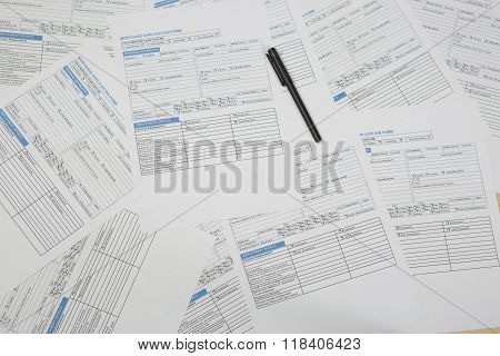 Black pen sitting on top of mortgage application papers
