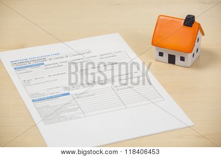 Mortgage application form with foam house sitting to the side