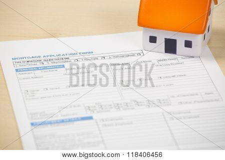 Foam house sitting on mortgage application papers
