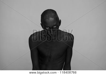 Gothic And Halloween Theme: A Man With Black Skin Is Isolated On A Gray Background In The Studio, Th