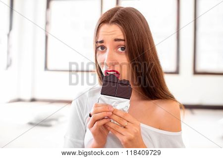 Woman with disappointed emotions holding chocolate