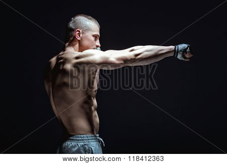 Side View Of Male Fighter Makes Punch On Black Background