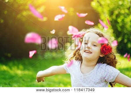 Happy Child Hand Up, Enjoying Freedom With Flying Flower Petals In The Air. Freedom Concept.