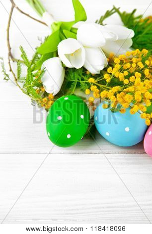 Easter eggs with spring flowers on white wooden board