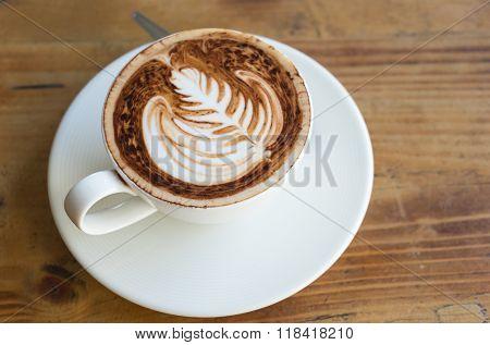Latte Art Fern Leave Pattern Of Cappucinno On A Wooden Floor (top View)