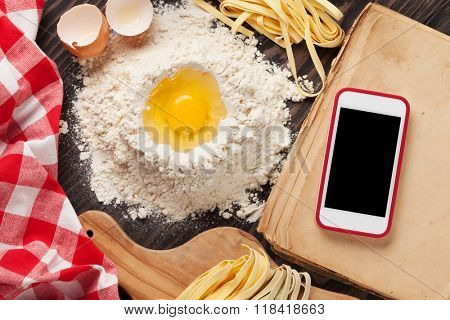 Homemade pasta cooking and smartphone with blank screen for your app over cooking book on wooden table. Top view