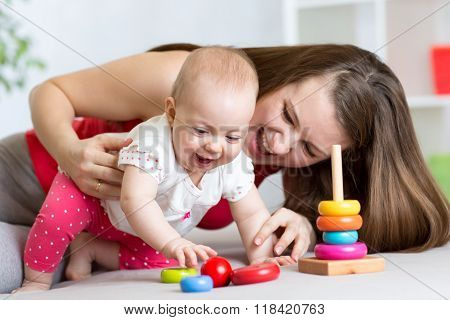 little child girl and her mommy play with color toys at home