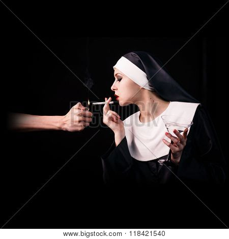 Smoking young nun with wineglass