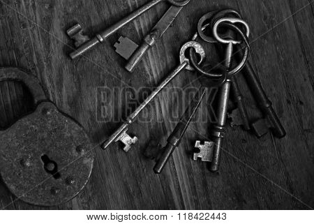 Black and white image of antique skeleton keys and padlock on dark, rustic wood background.  Low key still-life with natural, directional lighting for effect.