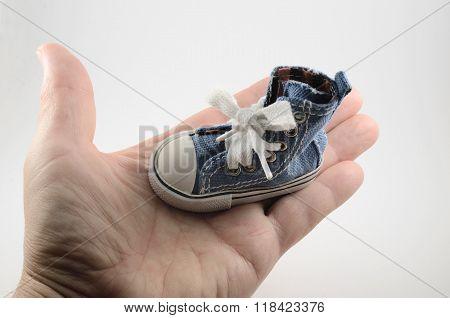 Tiny Denim Shoe On The Palm