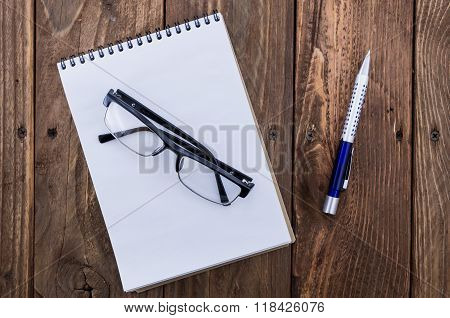 The Black Plastic Glasses On The Opened Notepad