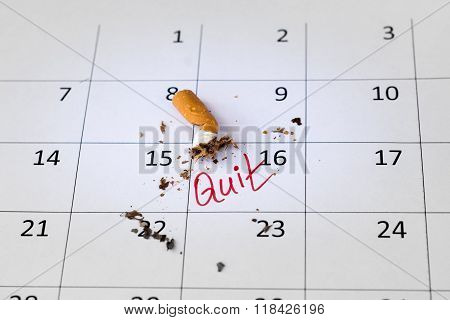 On the calendar, lies a crumpled cigarette butt. On a calendar an inscription in red marker.