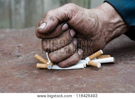 Hand man clenched. Fist of a man pushing a few cigarettes.