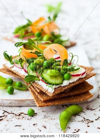 Healthy sandwiches with soft cheese and raw spring vegetables on crisp rye bread