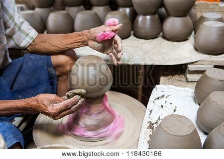 dirty hands making pottery in clay on wheel