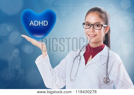 Female doctor holding heart with ADHD sign .