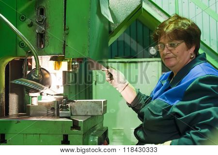 Senior female worker operates metalworking machine