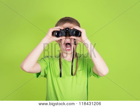 Surprised Young Boy With Binoculars On Green Background. Shocked Kid With Open Mouth Looking Through