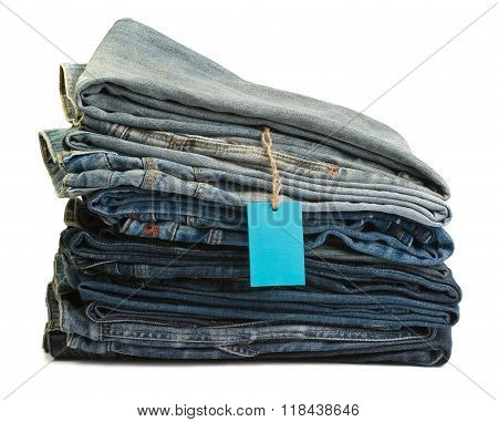Stack of blue denim clothes on white background, jeans