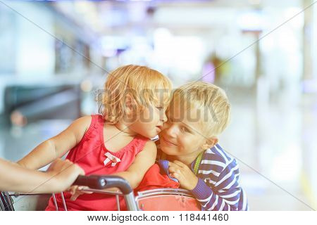 Happy cute little girl and boy at airport on luggage cart