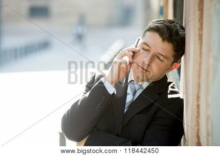Young Attractive And Busy Businessman With Closed Eyes Wearing Suit And Tie Talking Business On Mobi