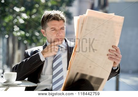 Attractive Businessman Sitting Outdoors Having Coffee Cup For Breakfast Early Morning Reading Newspa