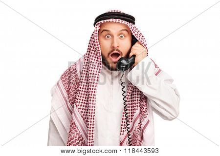 Studio shot of a surprised young Arab speaking on telephone isolated o white background