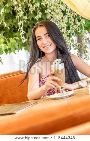 outdoor portrait of young happy woman in street cafe