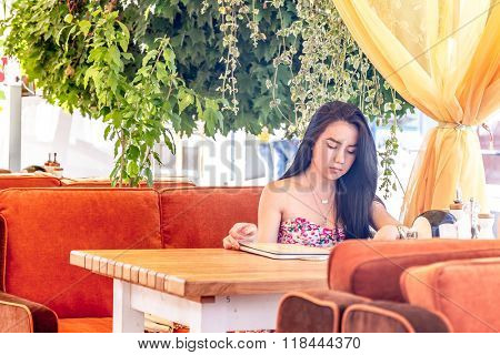 outdoor portrait of young happy woman reading menu in street cafe