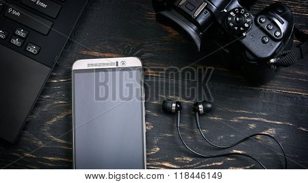 Laptop, smart phone, photo camera and headset on wooden background