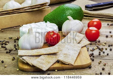 Crispbread with tomatoes, garlic, avocado and cheese on the table