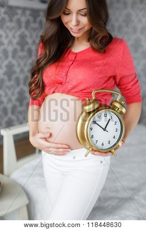 Pregnant woman with big clock in hand