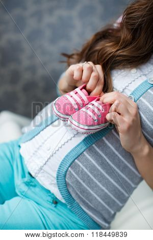 Happy future mother with pink booties in hand