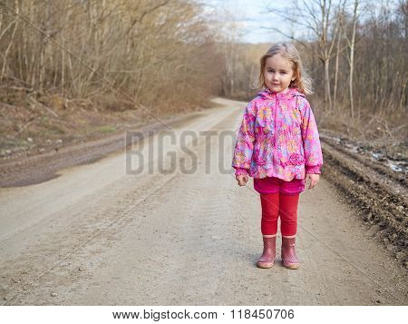 Cute Little Girl Standing On A Forest Road
