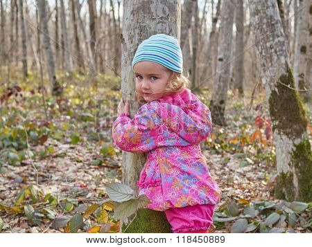 Cute Little Girl Hugging A Tree Trunk In The Spring Forest.