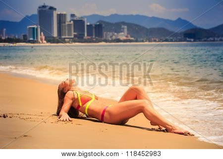 Blonde Girl In Bikini Sits On Seat Leans On Hands Smiles